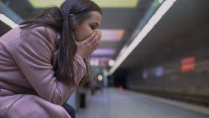 Femme angoissée sur un quai de métro. Crise d'angoisse, attaque de panique